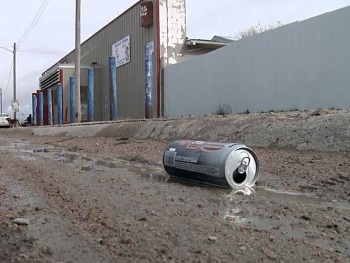 A beer can floats in a muddy ditch in Whiteclay Nebraska