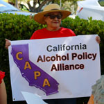 Woman in large hat proudly holds up CAPA California Alcohol Policy Alliance banner